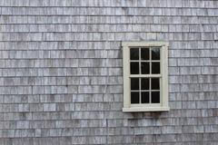 Wood shingles with window. Weathered wood shingles create background around a glass pane window Royalty Free Stock Photography