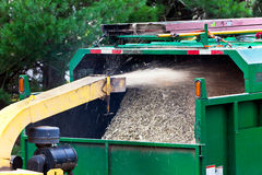 Wood shredder. Branches being shredded into wood-chips and blown into the back of a truck Stock Photos