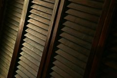 Wood shutters in low light. Antique wood shutter in low light, old window shutters inside royalty free stock photography