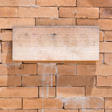 Wood sign on a brick wall Stock Photo