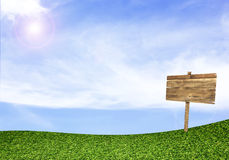 Wood sign on green field under blue sky. Background Royalty Free Stock Photography