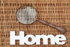 Wood Sign Home And Magnifying Glass On Rustic Wicker Background Stock Image