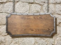Wood sign with metal frame on old stone wall stock image