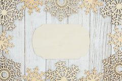 Wood sign with wood snowflakes on weathered whitewash textured wood background. With copy space for your message royalty free stock photo