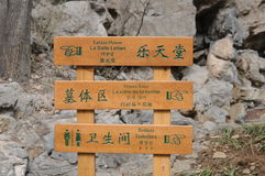 Wood signs including mandarin version of toilets, grave area and finger pointing symbols Royalty Free Stock Image