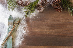 Wood skis on a wooden background. Green wood skis with sticks and a snowy fir branch with cones on a wood and snowy background Royalty Free Stock Image