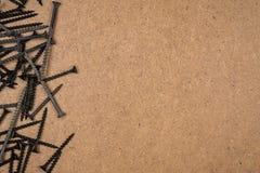 Wood skruvar på ljus - brun fibreboard Arkivbilder