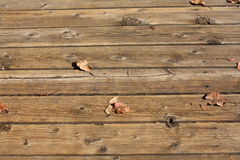 Wood slats of an outdoor deck. Weathered dark brown wooden slats forming a deck.  Knot holes and nails are in the wood.  Wood is probably Douglas fir Royalty Free Stock Photography