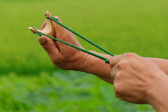 Wood slingshot catapult and hands. Daytime Royalty Free Stock Photos