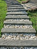 Wood and small white rocks pathway on grass in the garden. Beautiful wood and small white rocks pathway on grass in the garden Stock Photo