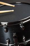 Wood snare drum. Drumsticks playing on a wood snare with black drum skin Stock Photos