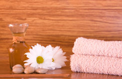 Wood spa. Spa oil, flowers and towels on wood background Stock Photos