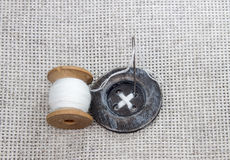 Wood spool with white thread, needle and sewn Stock Images