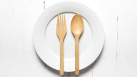 Wood spoon and fork with dish. Over white table background Royalty Free Stock Photo