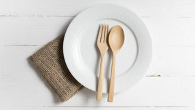 Wood spoon and fork with dish. Over white table background Royalty Free Stock Image