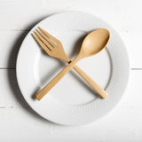 Wood spoon and fork with dish. Over white table background Stock Image