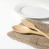 Wood spoon and fork with dish. Over white table background Royalty Free Stock Photography