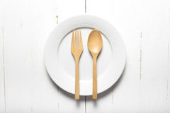Wood spoon and fork with dish. Over white table background Royalty Free Stock Photos