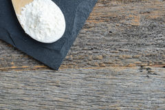 Wood Spoon Full of Flour on Slate Cutting Board and Wood Backg Stock Photography