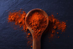 Wood spoon with paprika powder. Wooden spoon with paprika powder around over a black stone table Royalty Free Stock Photo