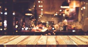 Wood stång för tabellöverkant med bakgrund för suddighetsnattkafé arkivfoton