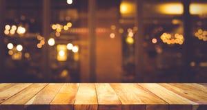 Wood stång för tabellöverkant med suddighetsljusbokeh i mörkt nattkafé Arkivbilder