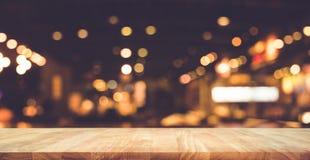 Wood stång för tabellöverkant med suddighetsljusbokeh i mörkt nattkafé
