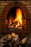 Wood stack and logs burning in brick fireplace. Wood stack and logs burning in indoor brick fireplace in country cottage Royalty Free Stock Images