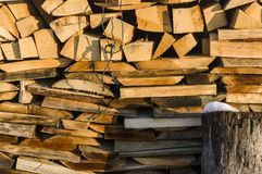 Wood stack of neatly stacked firewood and small wood to dry for. Firewood, firewood, raw material, wood rental with snow remains and chopping block Royalty Free Stock Image