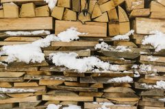 Wood stack of neatly stacked firewood and small wood to dry for. Firewood, firewood, raw material, wood rental with snow remains Royalty Free Stock Photo