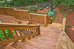 Wood Stairway to Landscaped Yard. Wood stairs and deck area leading to a landscaped seating area in a yard stock photos