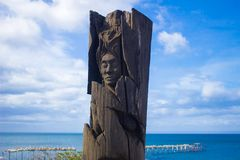 Wood Statue of an indigenous with the see behind in Punta Arenas, Chile centred. América del Sur Stock Image