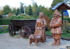 Wood statue of ukrainian peasants. And cart in the garden Royalty Free Stock Images