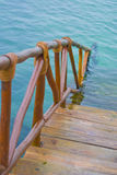 Wood steps. Wooden steps to water below. Blue clean and clear water in a bay. Cancun, Mexico. the steps and wood handrail lead into the water stock photos