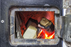 Wood stove firebox with fire and wood Royalty Free Stock Photo