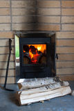 Wood stove, firewood and poker Stock Photo