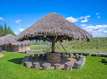 Wood and straw hut. With several wooden logs as chairs Stock Photography