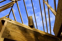 Wood Stud Roof Frame of Home Construction. Blue sky seen through the wood stud frame of a roof in the construction of a new home stock image