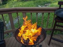 Open grill with big yellow orange flame getting ready to barbecue some food on an outside country deck gathering stock photography