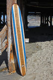 Wood surfboard against California beach pier. Stock Images