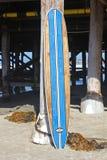 Wood surfingbräda mot den Kalifornien strandpir royaltyfri foto