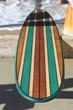 Wood surfingbräda mot den Kalifornien strandpir arkivbild