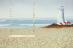 Wood swing on a sandy beach with a lighthouse royalty free stock photos
