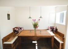 Wood tabell för familjstil med vita väggar och ett fönster med solen som in skiner arkivbild
