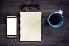 Wood tabell för kontor med den tomma notepaden, blyertspenna, exponeringsglas, telefon och Royaltyfria Bilder