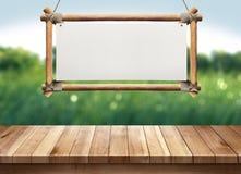 Wood tabell med att hänga trätecknet på suddig bakgrund för grön natur Royaltyfri Bild