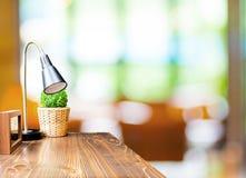Wood tabell med lamp- och bildramen på suddiga trädgårds- kafélodisar Royaltyfria Foton