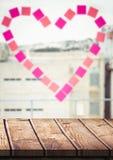 Wood tabell mot fönster med klibbiga anmärkningar för hjärta Arkivfoto