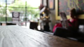 Wood tabell på suddigt folk i restaurangbakgrund lager videofilmer