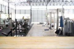 Wood tabell som är tom med rum för idrottshallkonditionutbildning i bakgrund royaltyfri fotografi